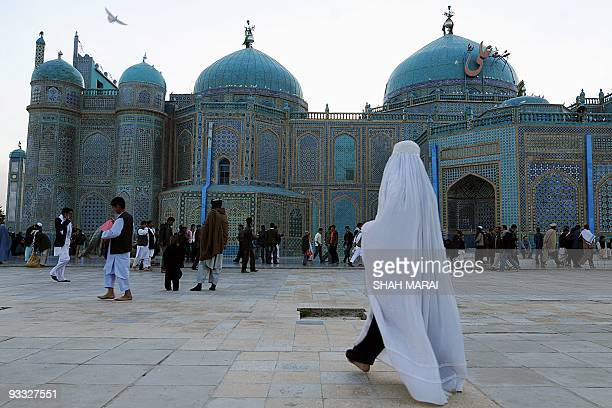 A burqaclad woman walks at the Hazrat Ali Shrine in the northern town of MazariSharif in Balkh province on March 19 2009 Tens of thousands of Afghans...