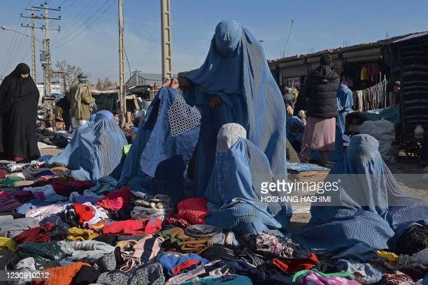 Burqa-clad women sell clothes along on a roadside in Herat on February 1, 2021.