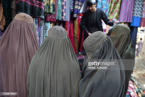 Burqa-clad women shop at a women's clothing store in Kandahar on October 1, 2020.