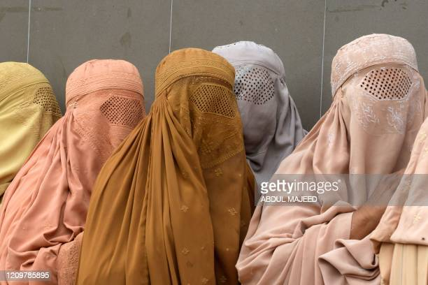 Burqa-clad women wait for to their turn to collect cash through a mobile wallet under the governmental Ehsaas Emergency Cash Programme for families...