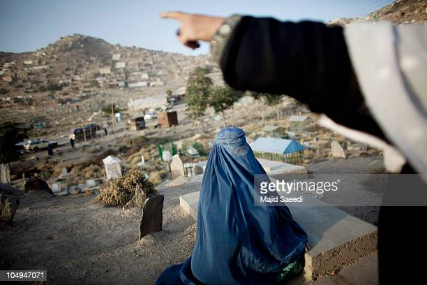 A burqacovered woman reads the Sura AlFatiha verse of the Koran over the grave of a relative in the graveyard October 7 2010 of Kabul's Saghi...