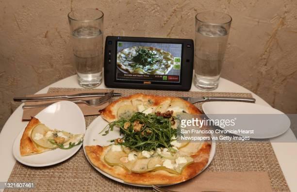 Burrata and apple pizza next to a new tablet that restaurants can put at every table for do-it-yourself ordering and paying the bill at Calafia in...