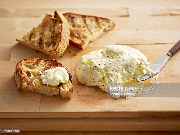 Burrata on wooden cutting board with toasted bread