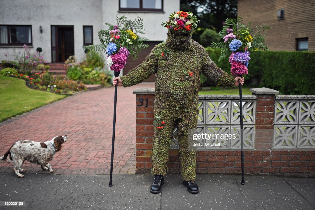 Burryman Andrew Taylor meets resident as he parades through the town encased in burrs on August 11, 2017 in South Queensferry, Scotland. The parade takes place on the second Friday of August each year and although the exact meaning of this tradition has been lost through the years though it is thought to have begun in the Seventeenth century. The tradition is believed to bring good luck to the towns people if they give him whisky offered through a straw or a donation of money.