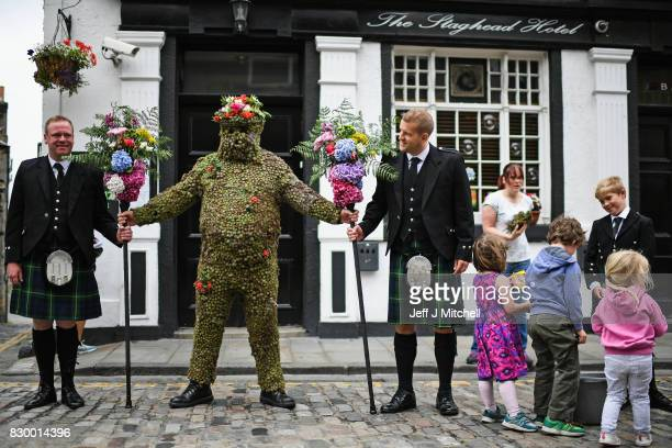 Burryman Andrew Taylor meets residents as he parades through the town encased in burrs on August 11 2017 in South Queensferry Scotland The parade...