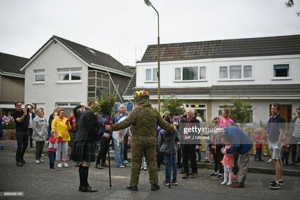 Burryman Andrew Taylor with assistants Andrew Findlater and Duncan Thompson meet resident as he parades through the town encased in burrs on August 11, 2017 in South Queensferry, Scotland. The parade takes place on the second Friday of August each year and although the exact meaning of this tradition has been lost through the years though it is thought to have begun in the Seventeenth century. The tradition is believed to bring good luck to the towns people if they give him whisky offered through a straw or a donation of money.
