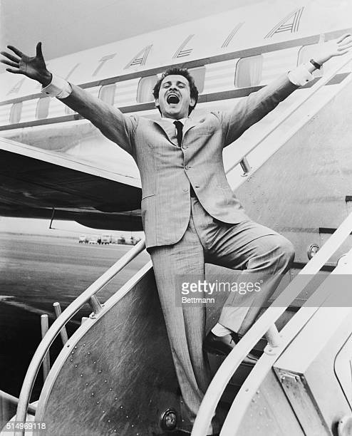 Bursting into song Italian recording star Domenico Modugno serenades New York after his arrival from Rome aboard an Alitalia Airlines plane He'll...