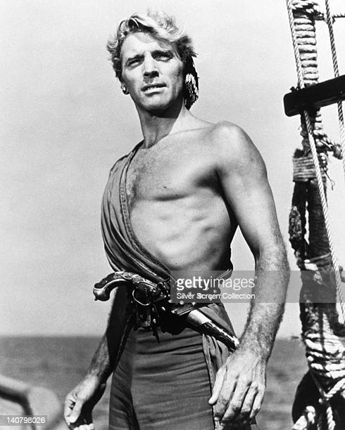 Burt Lancaster US actor bare chested but for a sash with a musket tucked in his belt in a publicity portrait issued for the film 'The Crimson Pirate'...