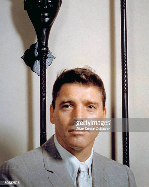 Burt Lancaster US actor wearing a grey jacket over a white short and white tie in a studio portrait circa 1965