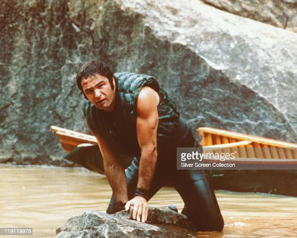 Burt Reynolds US actor holding onto some rocks as he struggles in the water with his boat behind him in a publicity still issued for the film...