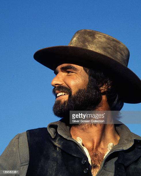 Burt Reynolds US actor wearing a full beard a cowboy hat and a black leather waistcoat in a publicity still issued for the film 'The Man Who Loved...
