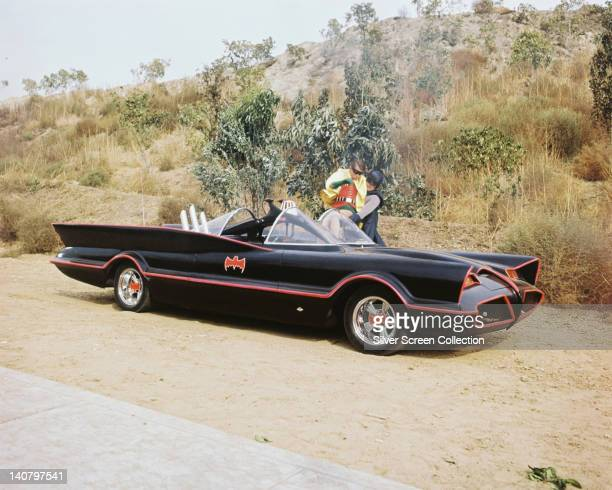 Burt Ward US actor and Adam West US actor both in costume as the 'Dynamic Duo' with the Batmobile in a publicity still issued for the television...