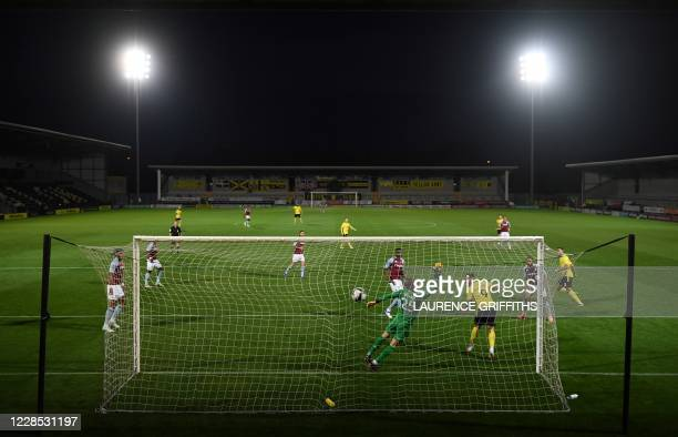 Burton Albion's English defender Colin Daniel scores the opening goal during the English League Cup second round football match between Burton Albion...