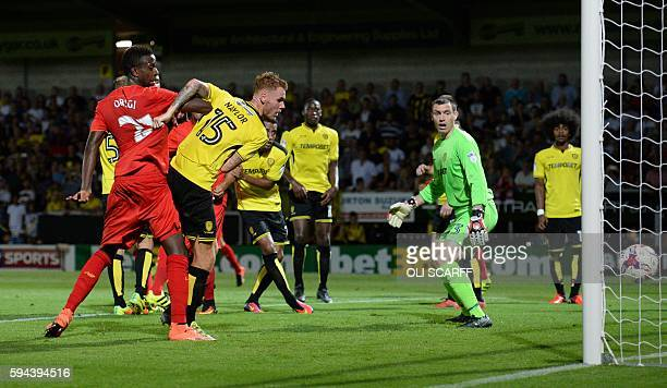 Burton Albion's English midfielder Tom Naylor scores on own goal for Liverpool's third during the English League Cup second round football match...