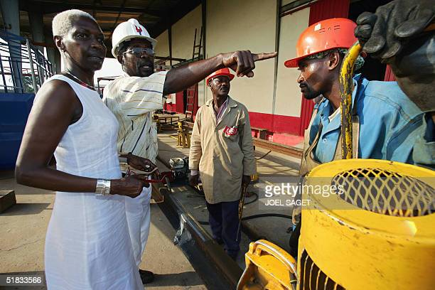 Burundi 's Princess Esther Kamatari and France's first black model listens to an employee as she paid a visit to a plant in Douala Cameroon 29...