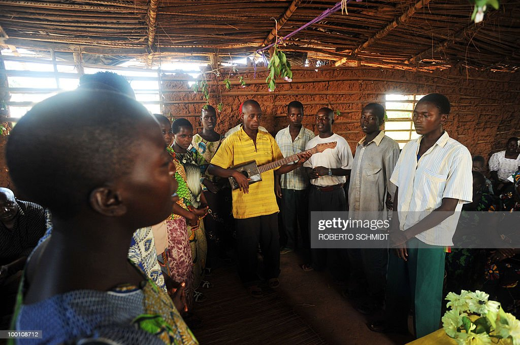 Burundian man plays a guitar made out of wood and a empty can of oil while leading others in song during a prayer service at their local church in a 'Peace Village' near the south-western Burundian town of Mutambara on May 13, 2010. Some 300 resident families who live in Peace Village are part of a larger group of some 500,000 Burundian refugees who have come back to Burundi since 2002 after having fled to neighboring countries running away form a bloody 13-year civil war.