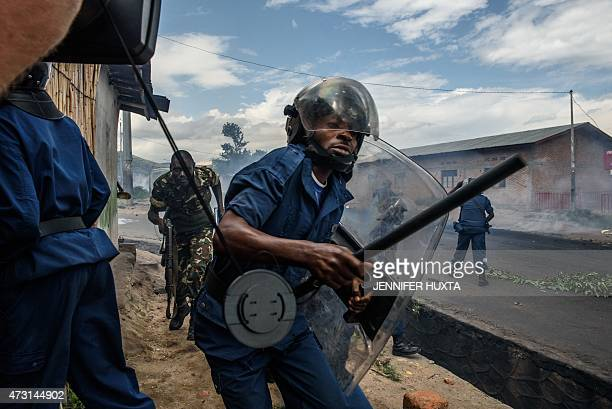 Burundian police officer holding a baton and army forces run after protestors throwing stones during a demonstration against incumbent president...