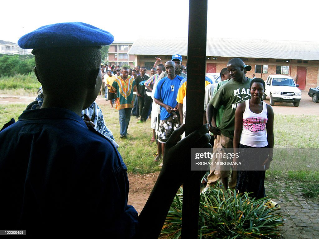 A Burundian police officer watches voters line up outside a polling station on May 24, 2010 in the capital Bujumbura. Local polls kicked off on May 24 in Burundi, the first phase of an electoral marathon set to put the small, war-scarred African nation's peace deal and democratic credentials to the test. Polling stations opened at 6:00 am (0400 GMT), with some 3.5 million voters called to pick local councillors in a ballot seen a key test for presidential and legislative elections due in June and July respectively.