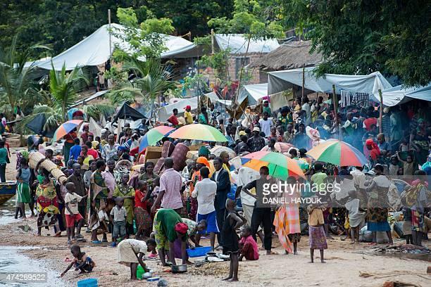 Burundian refugees gather along the shoreline of Lake Tanganyika in the fishing village of Kagunga on May 21 2015 UNHCR is transporting approximately...