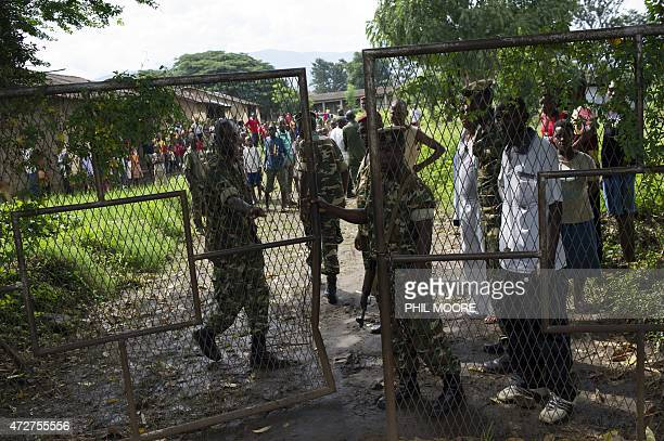 """Burundian soldiers close the gate of the Ngagare military camp after taking a man accused of being an """"Imbonerakure"""", a member of the ruling CNDD-FDD..."""