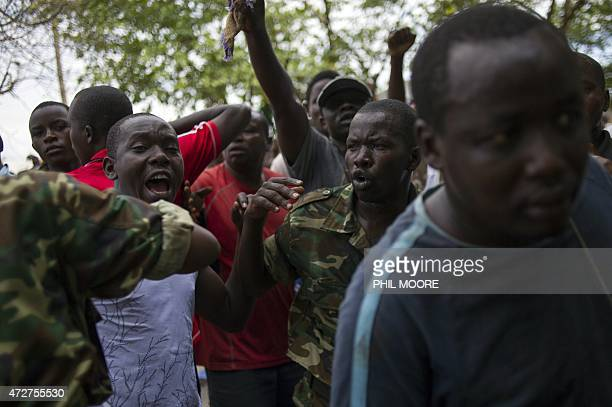 """Burundian soldiers hold back civilians after they caught a man accused of being an """"Imbonerakure"""", a member of the ruling CNDD-FDD party's youth wing..."""
