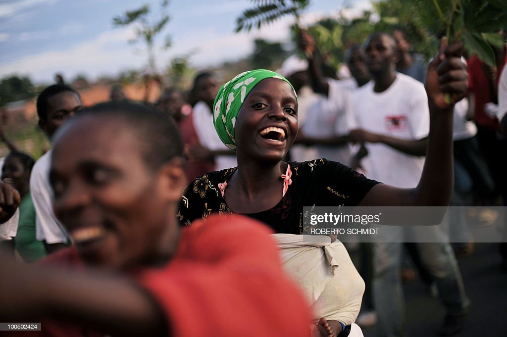 A Burundian woman smiles as she parades along other supporters during a political rally for the ruling party at a sports field in Bujumbura on May 11, 2010. Some 3.5 million registered voters will go to the polls to elect 1,935 municipal counselors across the country on May 20th in what experts agree will be a catlyst for the soon to follow Legislative and Presidential elections. This elections will be the fist all inclusive elections since a peace accord ended a bloody 13 year civil war in 2006. The French government has provided Burundi with 90,000 euros to organize the upcomming elections.