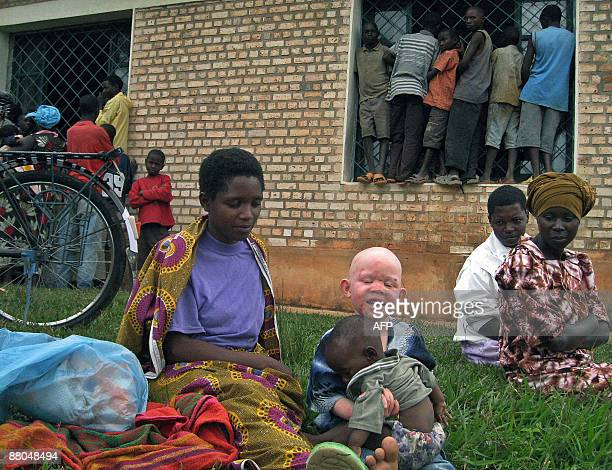 A Burundian woman with an albino child waits outside courtroom during a trial of some of 11 Burundians accused of being behind the murder of albinos...