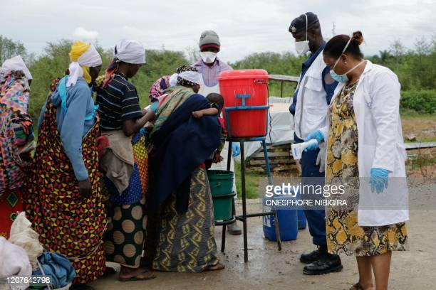Burundians wash their hands, as a preventive measure against the COVID-19 coronavirus, on their arrival of their repatriation in Gatumba, on the...