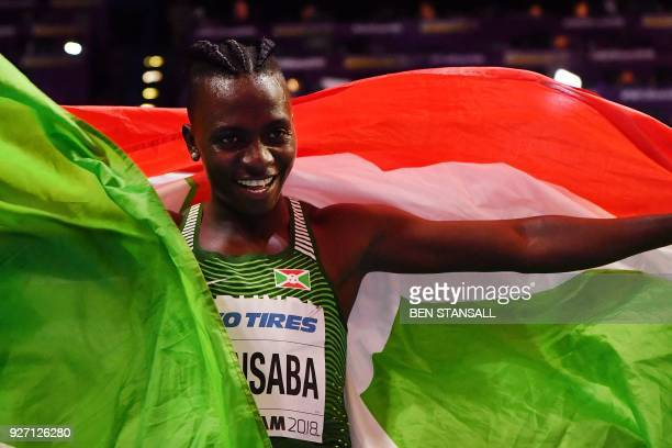 Burundi's Francine Niyonsaba celebrates with her flag after winning the women's 800m final at the 2018 IAAF World Indoor Athletics Championships at...