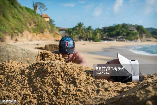 burying a person in sand at beach in mazunte, mexico - enterrar imagens e fotografias de stock