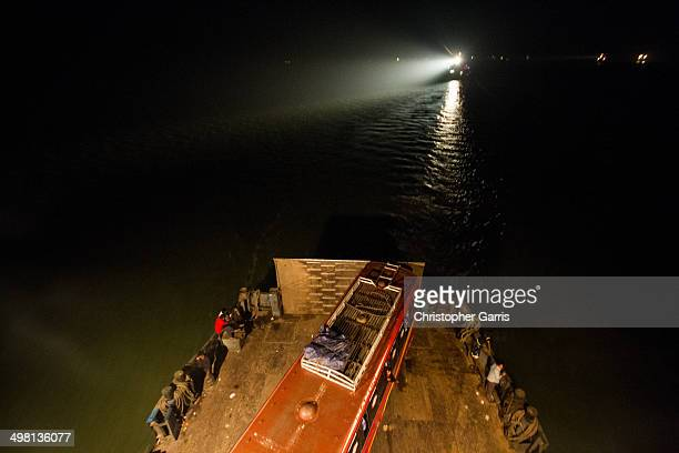 CONTENT] A bus and ferry passengers aboard a ferry as it crosses the Meghna River at night