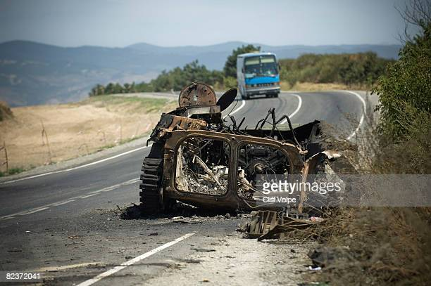 A bus approaches the burned out remains of a Georgian armored personnel carrier on the road August 15 2008 just outside Gori Georgia US Secretary of...