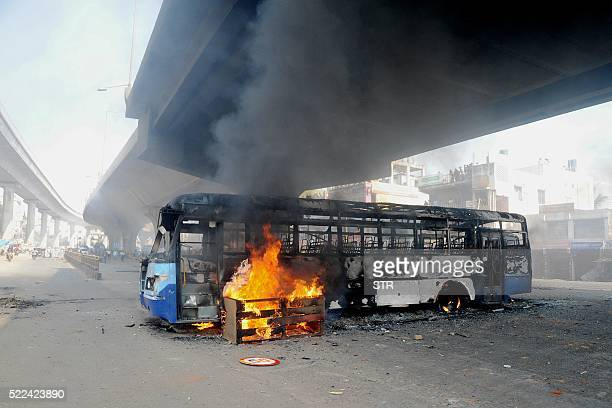 A bus burns underneath an flyover following a protest by Indian garment factory workers in Bangalore on April 19 2016 Thousands of garment factory...