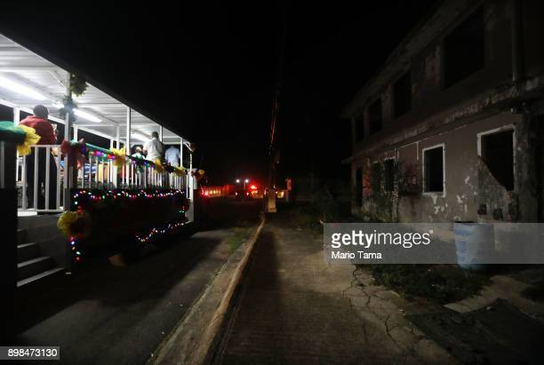 A bus carries musicians playing parrandas a Puerto Rican tradition similar to Christmas carols past an abandoned building without electricity in the...