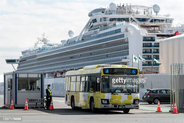 A bus carrying passengers who disembarked the quarantined Diamond Princess cruise ship drives past the cruise ship at Daikoku Pier on February 19...