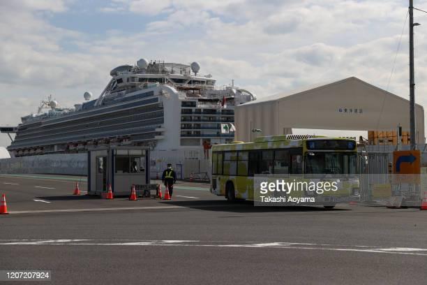 A bus carrying passengers who disembarked the quarantined Diamond Princess cruise ship leaves Daikoku Pier on February 19 2020 in Yokohama Japan...