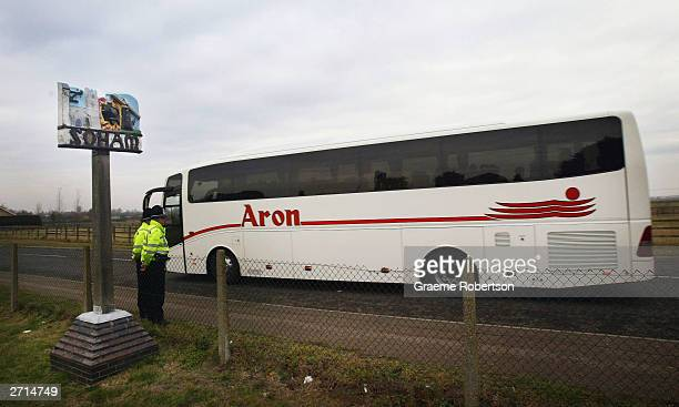 A bus carrying the members of the jury in the trial of Ian Huntley and Maxine Carr passes by two police officers November 10 2003 in Soham England...