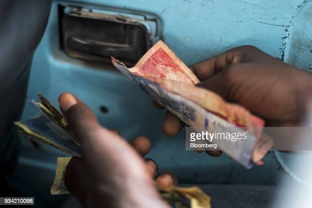 A bus conductor counts Ghana cedi banknotes as the bus waits in traffic in Accra Ghana on Thursday March 15 2018 Ghana wants to shake up the way it...