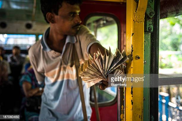 A bus conductor holds a fan of Indian rupee banknotes on a bus in Kolkata West Bengal India on Thursday Oct 31 2013 Indian stocks fell for the first...