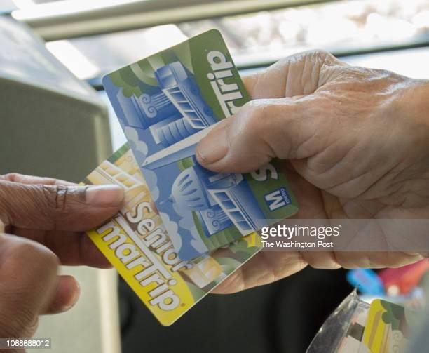 Bus driver Ajit Jayaweera shows Reston resident Joe Camarda how to swipe and add fare to Senior SmarTrip and SmarTrip cards aboard the MATT bus...