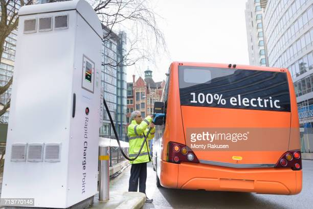 bus driver charging electric bus at charging station - electricity stock pictures, royalty-free photos & images