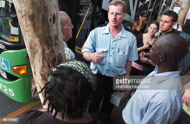 A bus driver deals with confused passengers in Brisbane 14 November 2005 after authorities in the east coast city ordered all buses and trains to...