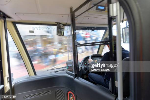 Bus driver driving electric bus in traffic