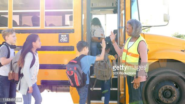 bus driver greets children boarding bus - school bus stock pictures, royalty-free photos & images