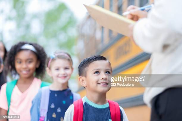 Bus driver greets school children