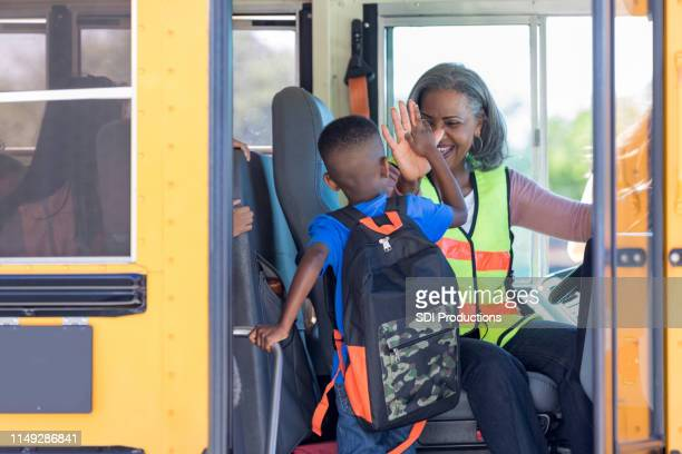 bus driver high fives new student stepping on bus - school bus stock pictures, royalty-free photos & images