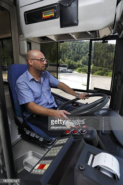 A bus driver in a blue shirt looking at the road