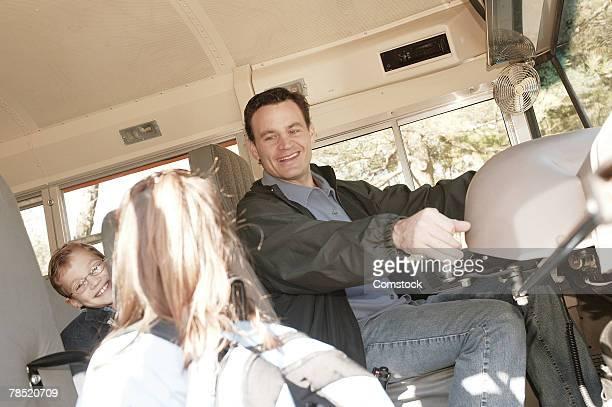 Bus driver opening bus door for girl
