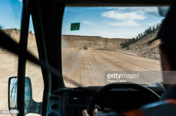 Bus Driver Rolling on Dirt Road in Open Phosphate Mine