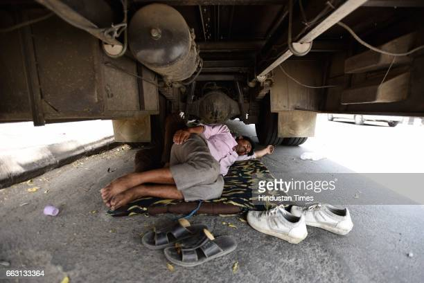 A bus driver taking an afternoon nap under a bus on Mathura Road on a hot sunny day on April 1 2017 in New Delhi India According to the India...
